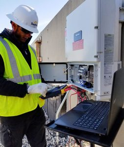 outdoor technician checking equipment with laptop